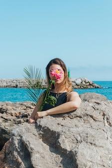 海の近くに立っている美しい花で彼女の顔を隠す女