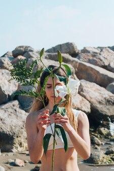 ビーチで彼女の顔の前に枝を保持している美しい女性