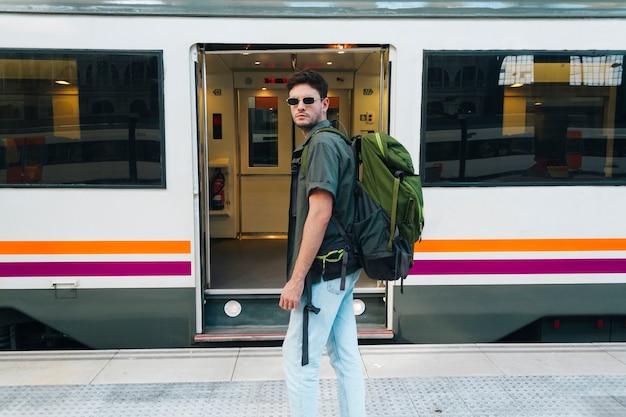 眼鏡をかけ、鉄道列車の前に立っているバックパックを運ぶスタイリッシュな男性の観光客