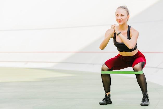 Женщина делает упражнения с резинкой