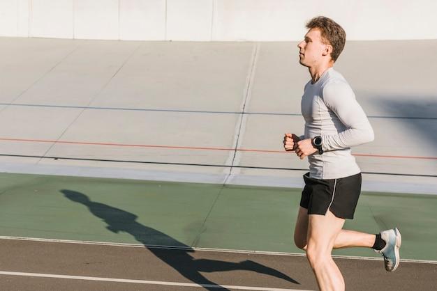 走っているスポーティな男の側面図