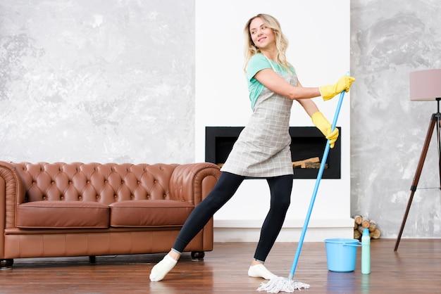 Женщина-экономка в фартуке танцует со шваброй во время работы по дому