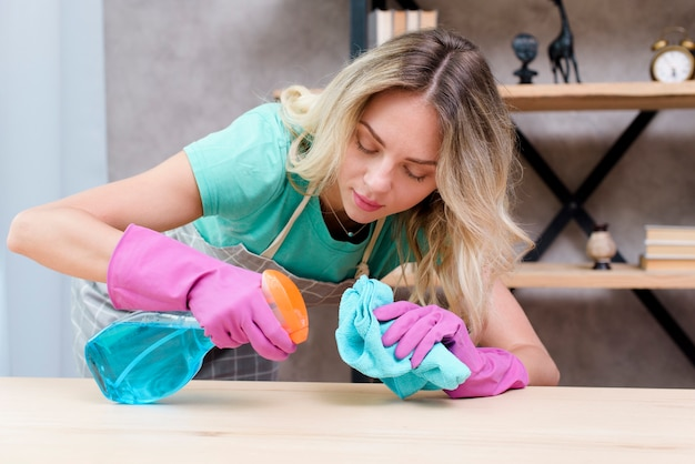 きれいな女性クリーナー、洗剤のスプレーと布で木製の机を掃除