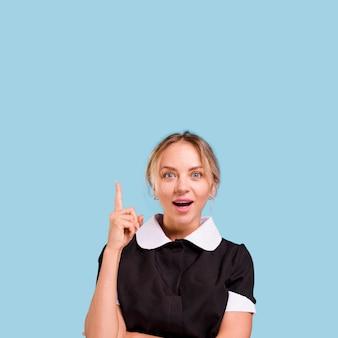 青い壁に対して新しい素晴らしいアイデアで上向きの方向を指している若い女性の肖像画
