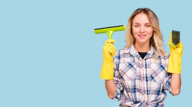 プラスチックワイパーとカメラを見て青い表面に対して立っているブラシを保持している若い笑顔の家政婦