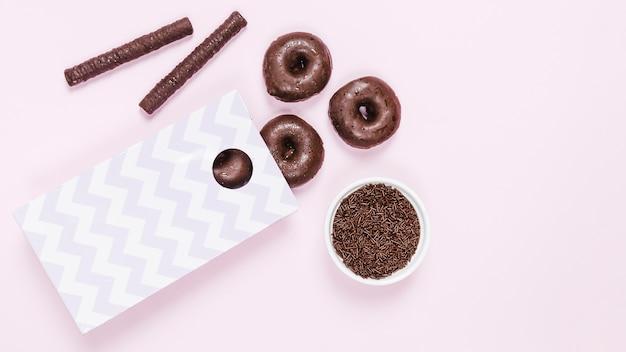 Вид сверху глазированные пончики и шоколадные палочки