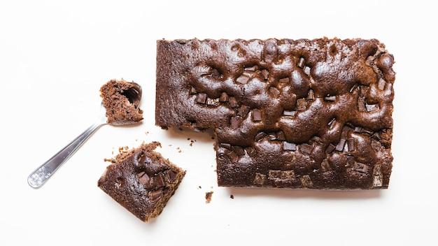 Плоский лежал темный шоколадный торт с ложкой
