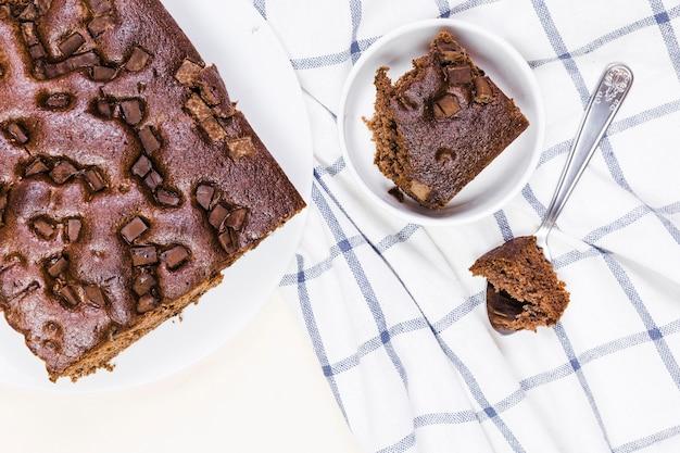 縞模様の布の上に横たわるフラットレイチョコレートケーキ