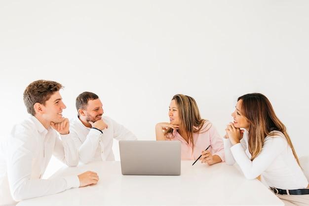 Коллеги обсуждают и смеются в офисе