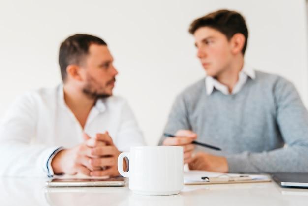 オフィスのテーブルの上の白いコーヒーカップ