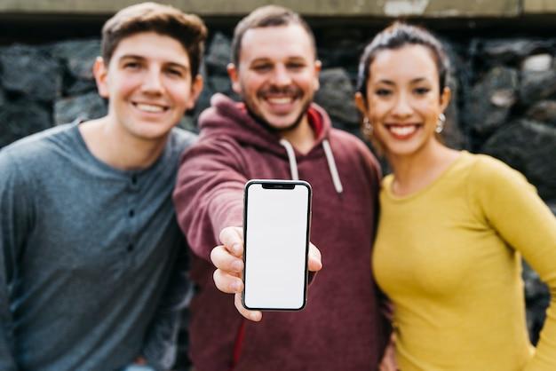 Молодой человек, показывая пустой экран смартфона, стоя возле многорасовых друзей