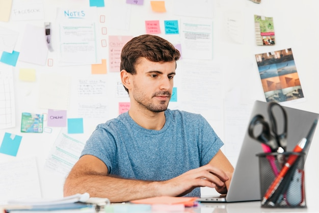 ノートを壁にノートパソコンで入力する若い男