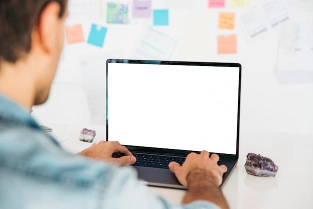 ノートを壁の近くの机でラップトップに入力する男