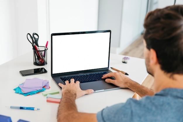 文房具を机にノートパソコンで入力する男