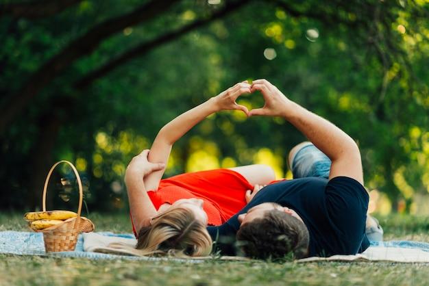 正面のカップルが空気中のハートの形を作る
