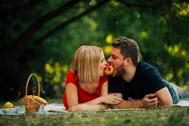 幸せなカップルの外のリンゴを食べる