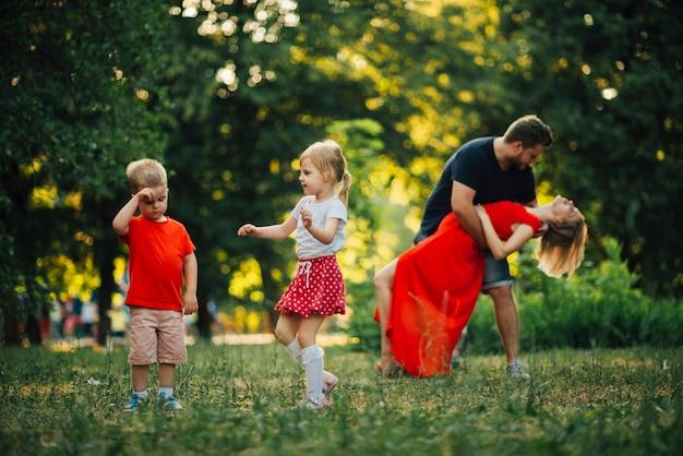 若い家族が公園で踊って