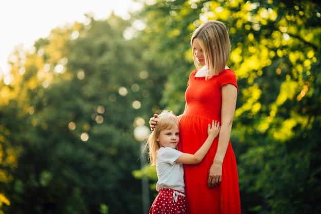 彼女の妊娠中の母親を抱いて娘