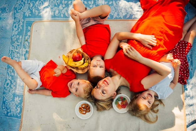 Мать и ее дети лежат на одеяле