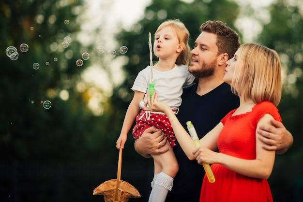 屋外のシャボン玉を吹く家族