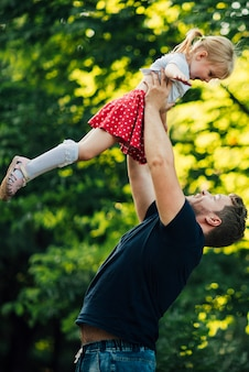 Отец держит свою дочь в воздухе