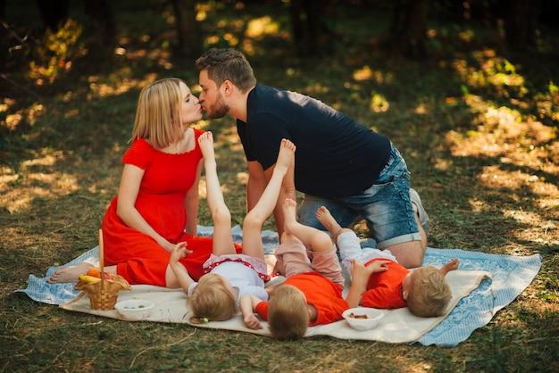 カップルがキスをし、子供たちと遊ぶ