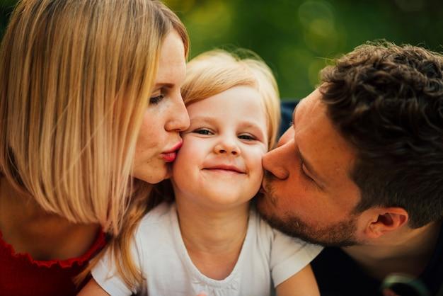 Счастливая пара целует ребенка крупным планом