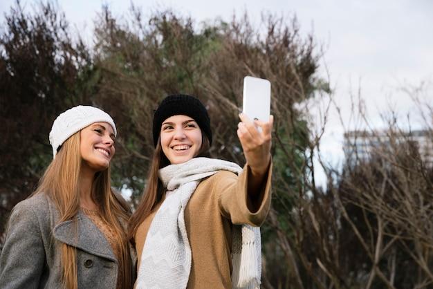 Средний снимок двух улыбающихся женщин, принимающих селфи