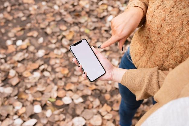 Крупным планом две молодые женщины, глядя на телефон