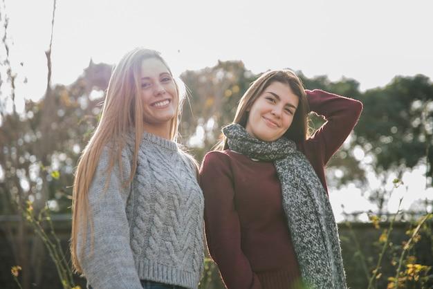 Средний снимок двух женщин, позирующих в парке