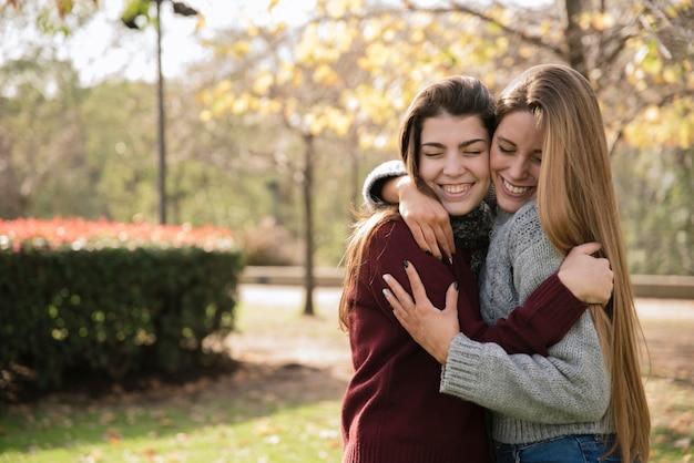 Средний снимок двух обнимающихся молодых женщин в парке