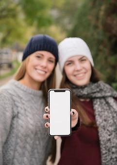 Средний снимок двух женщин, держащих телефон в руках