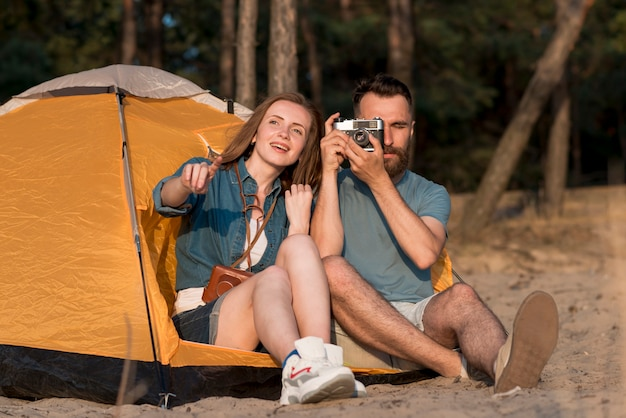 テントで写真を撮る座っているカップル