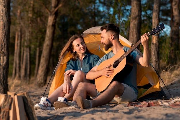 テントのそばに座って歌っているカップル