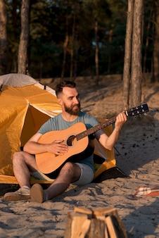 テントの横にあるギターを弾く男
