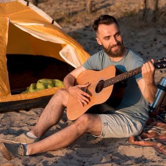 Счастливый человек играет на гитаре