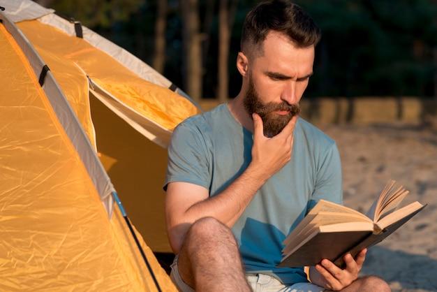 テントの横にある本を読んでいる人