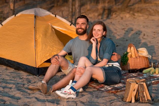 キャンプのカップルが一緒に座っています。