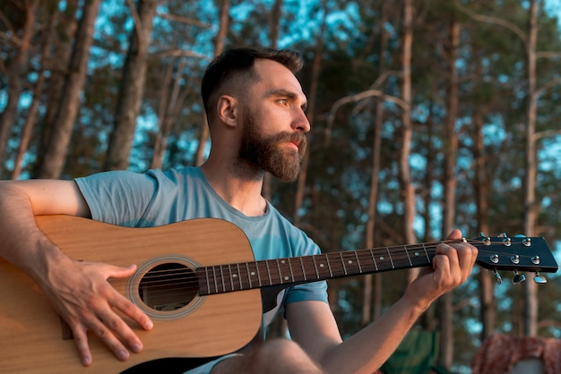Бородатый мужчина играет на гитаре