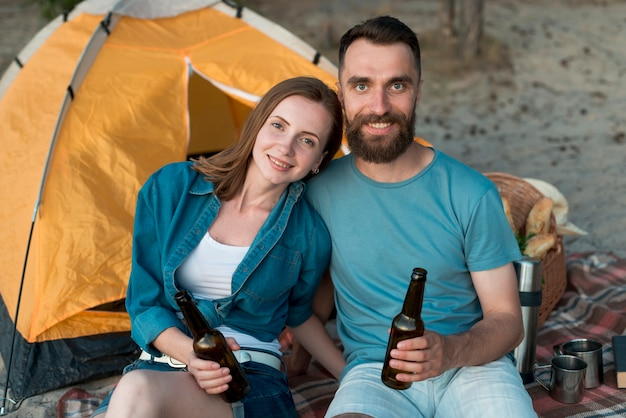 カメラを見て幸せなキャンプのカップル