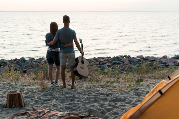 Пара смотрит на закат у воды