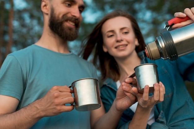 お茶を注ぐ幸せなカップルのクローズアップ