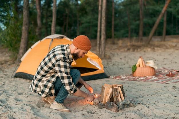 身をかがめる男、キャンプファイヤーに火を付ける
