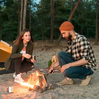 たき火を発火して身をかがめるカップル