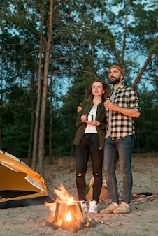 キャンプファイヤーでよそ見立っているカップル