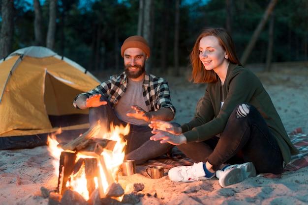 幸せなカップルのキャンプファイヤーでウォーミングアップ