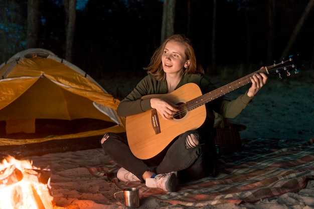 たき火でギターを弾く幸せな女の子