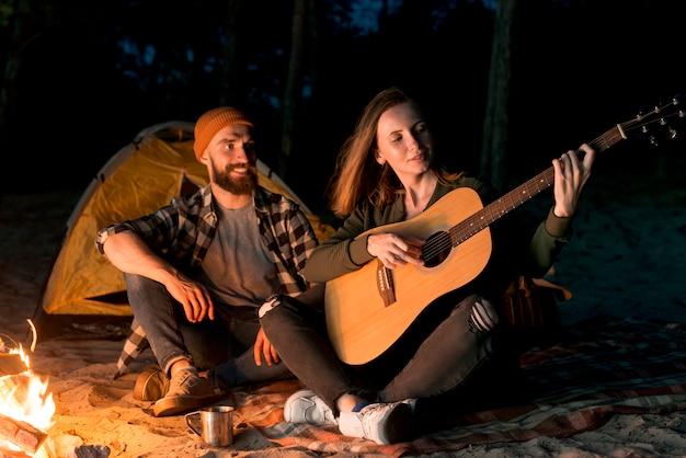 幸せなカップルの歌とギターを弾く