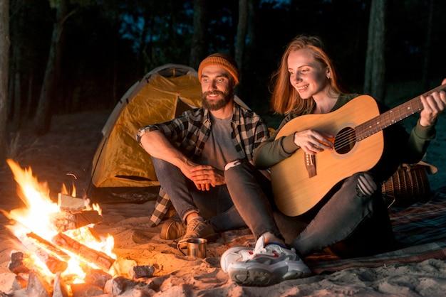 キャンプファイヤー付きのテントで歌っているカップル