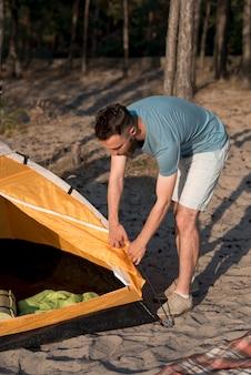 Стоящий мужчина разбирает палатку